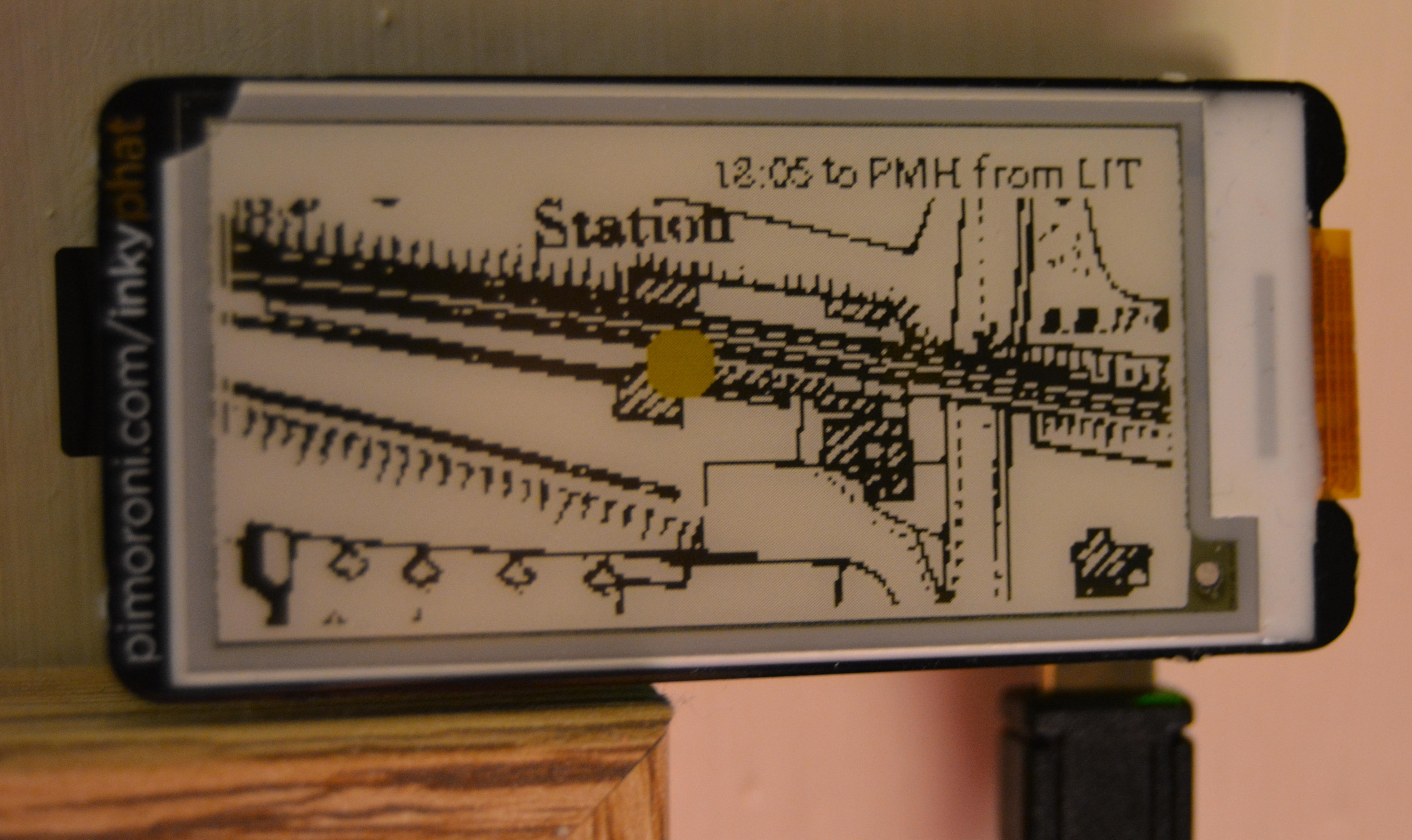 Photo of the station tracker e-ink display with a train at the platform